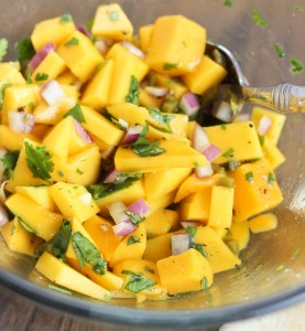 Diced mango and onion with cilantro in a bowl