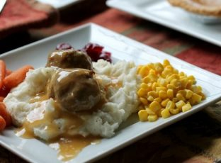 Thanksgiving meatballs on a mountain of mashed potatoes with corn, baby carrots and cranberry sauce