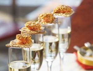 Shrimp DeJonghe Bites Resting Atop Champagne Flutes