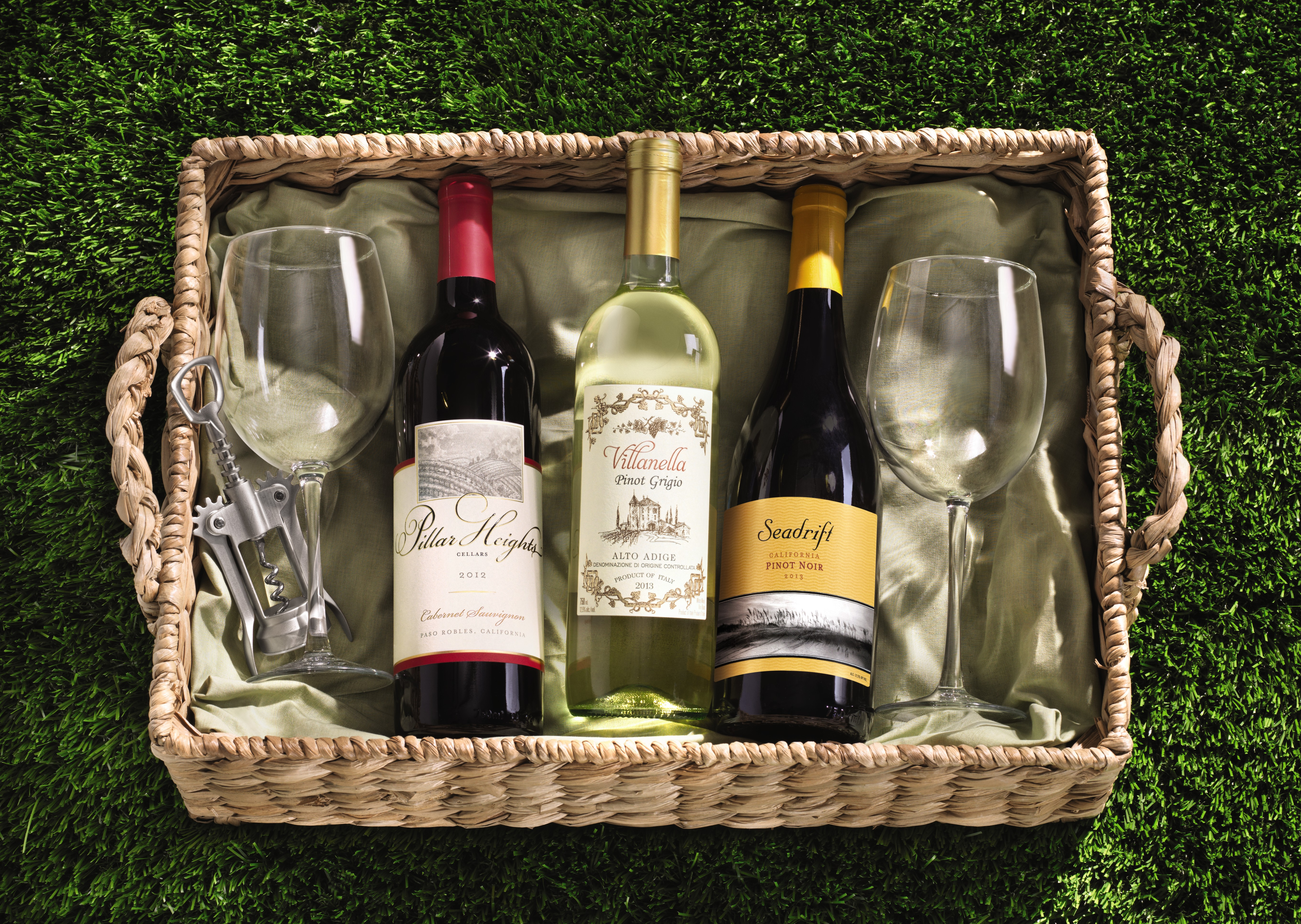 ALDI wine bottles in a picnic basket with glasses and a cork opener