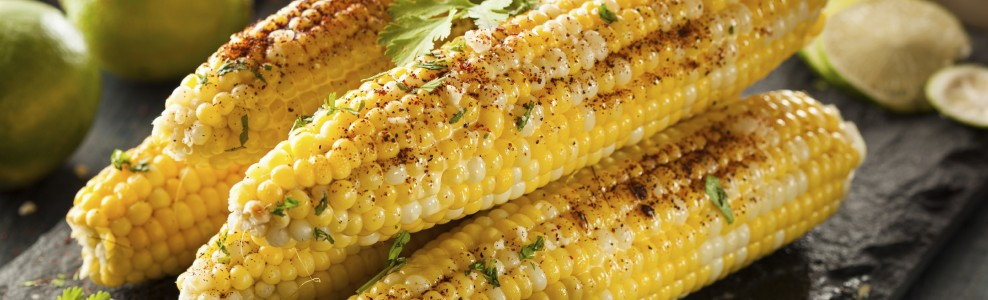 Grilled corn with garnish and limes