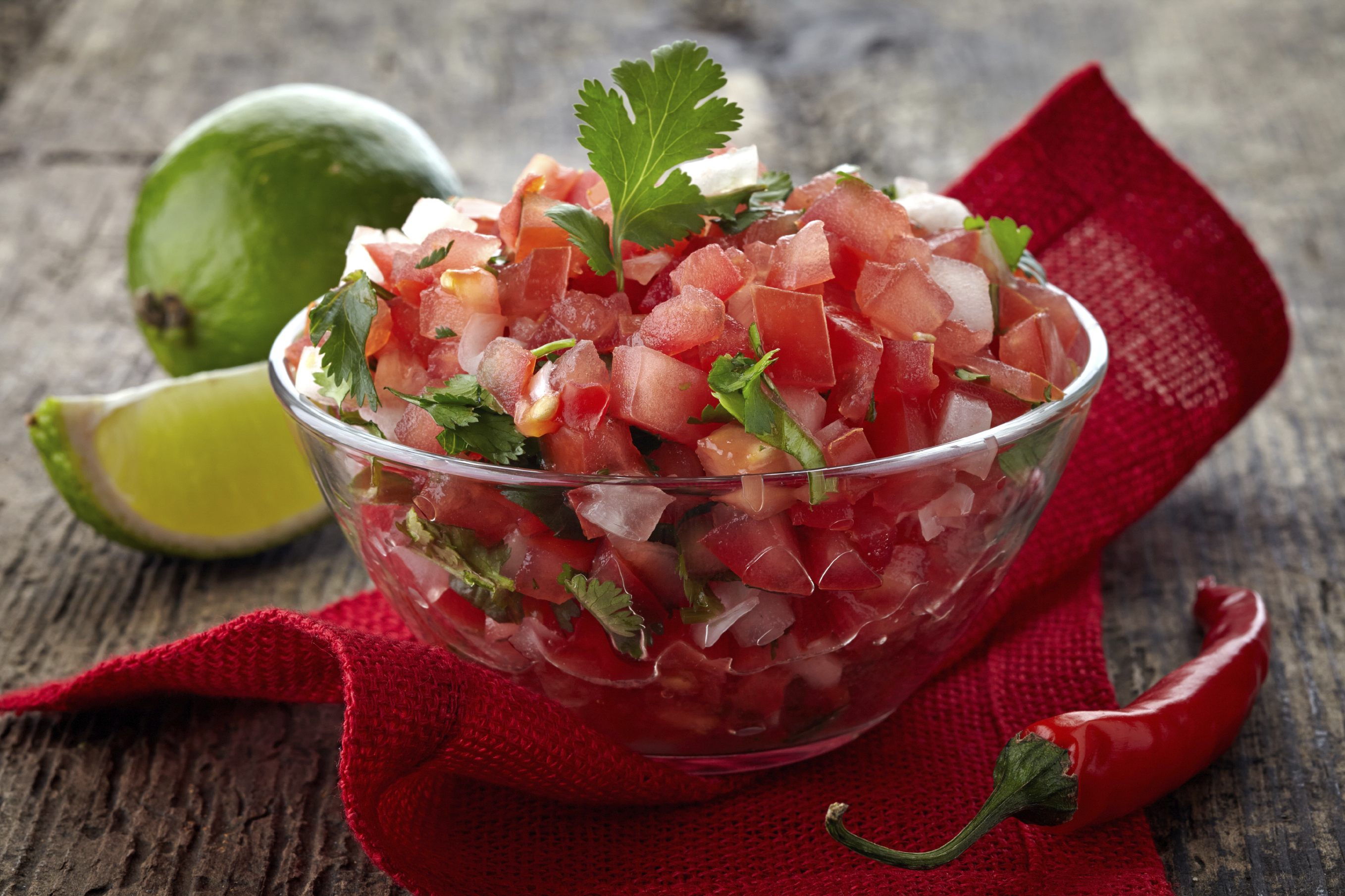 Chunky salsa in a bowl with limes on the side