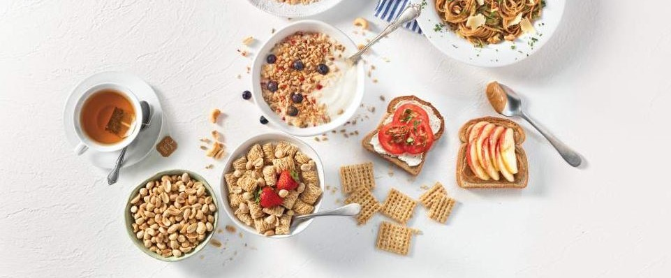 A variety of healthy breakfast options including cereal, nuts, and toast with nut butter and apples.