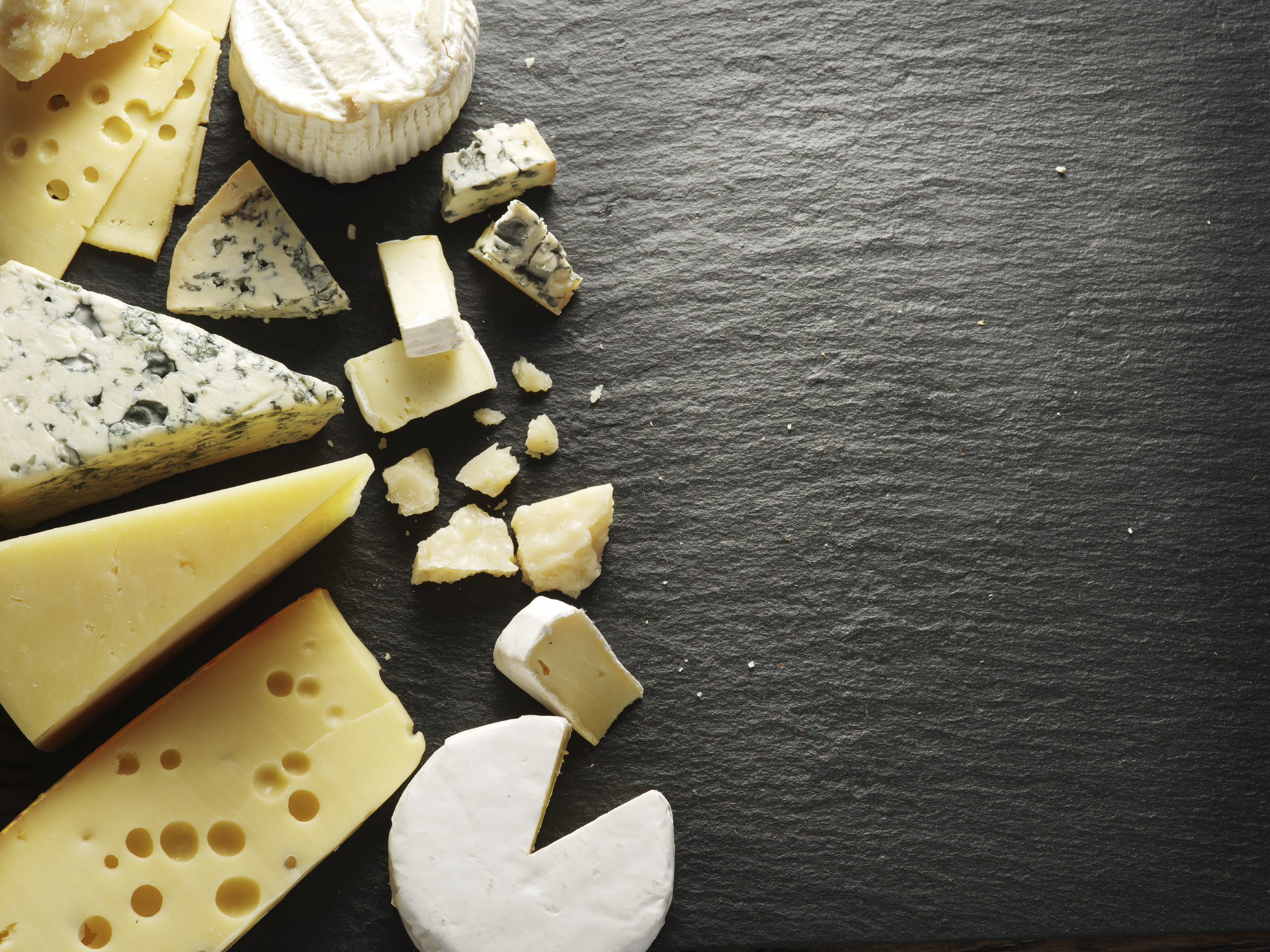 Various cheeses on a black board.