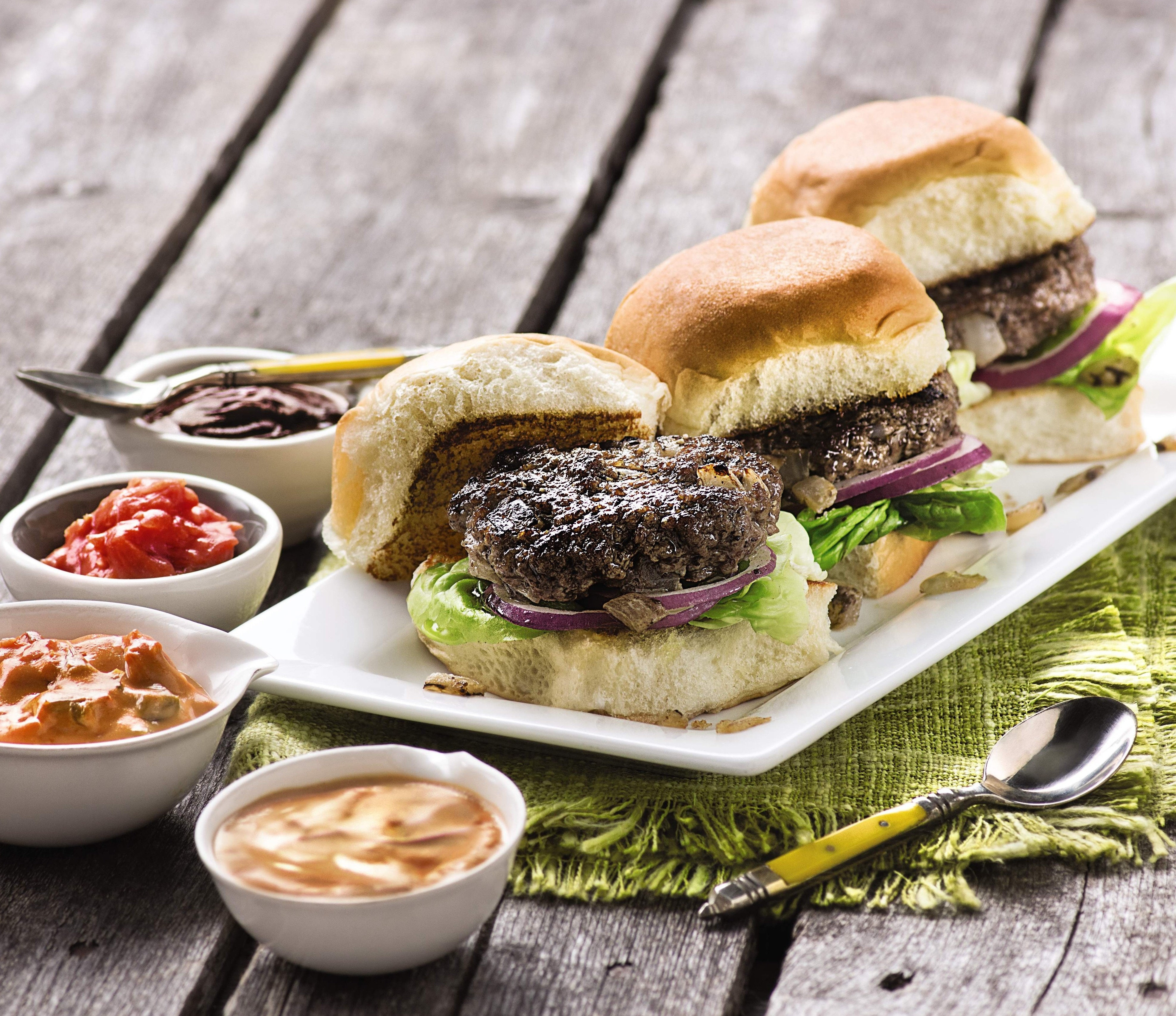 Grass fed ground beef burgers with various condiments.