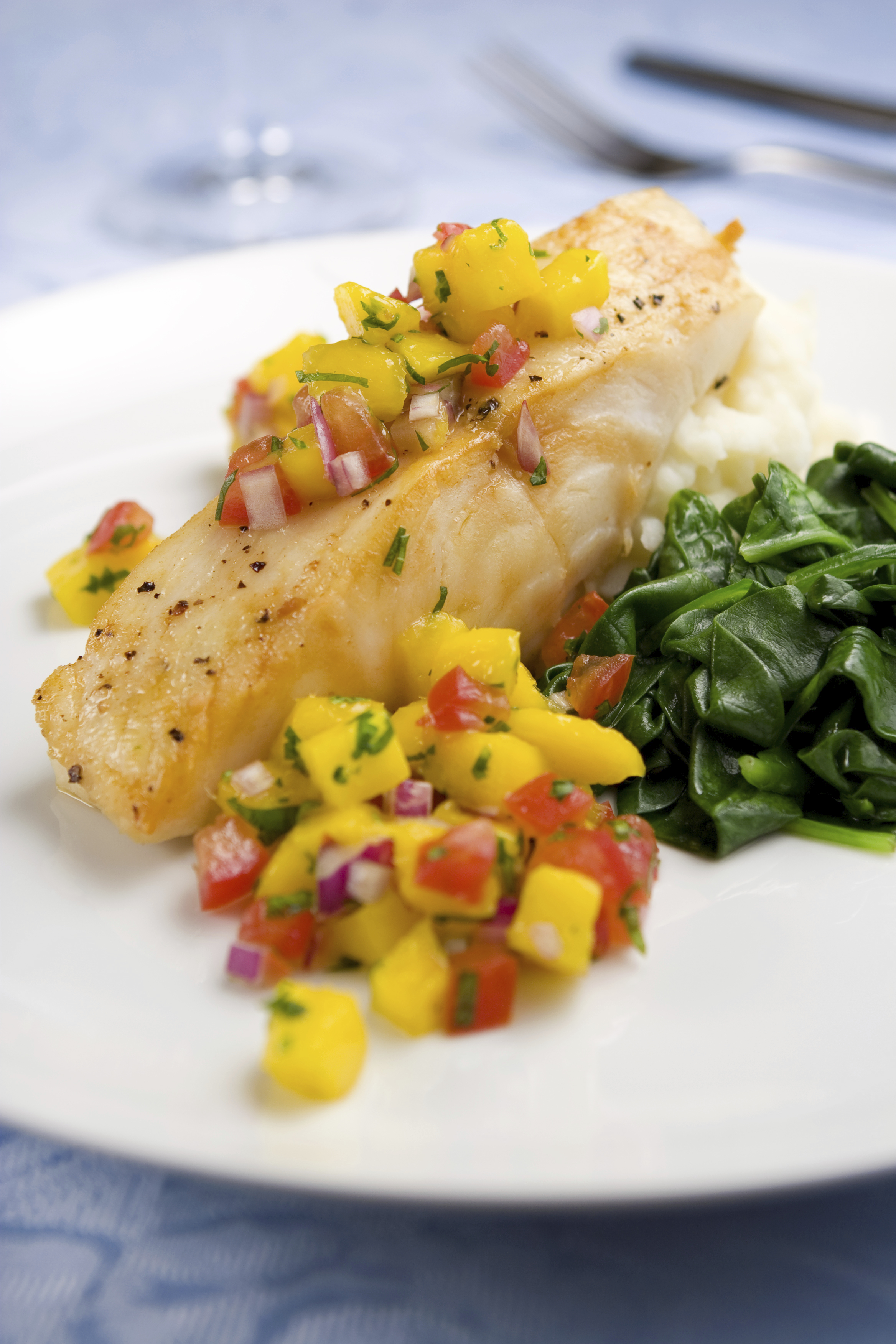 Grilled fish with mango salsa and sauteed spinach.