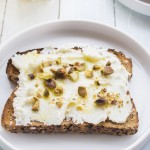 Ricotta spread on rustic toast, drizzled with olive oil and sprinkled with crushed pistachios