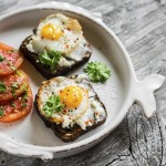 toast with feta cheese and fried quail egg, fresh tomatoes on a light wooden surface - a healthy Breakfast or snack
