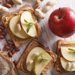 sandwiches with peanut butter and an apple. vertical view from above