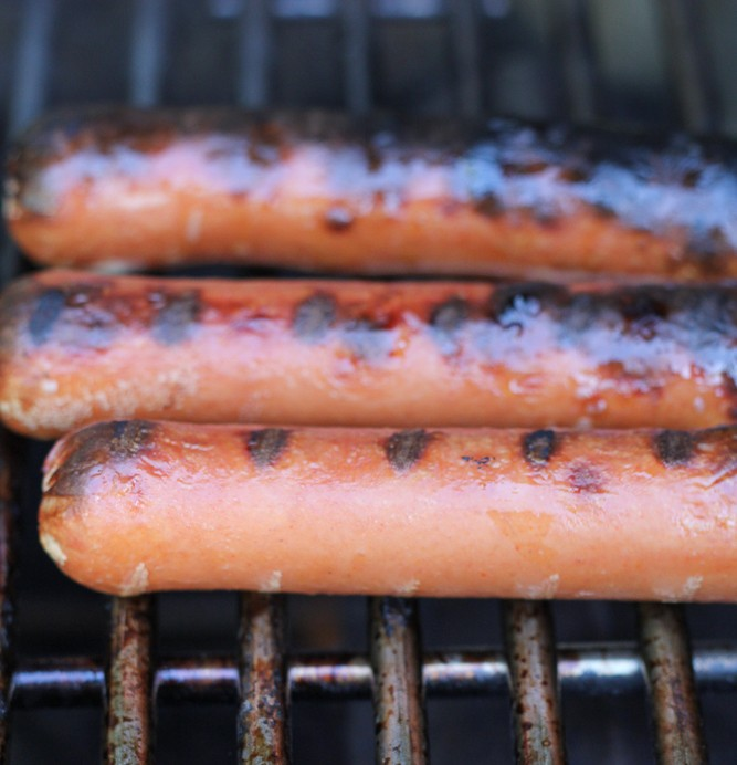 Hot dogs cooking on a grill.