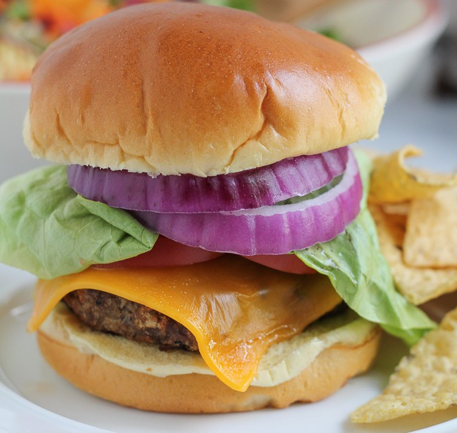 Cheeseburger with lettuce, tomato, and onion with tortilla chips on the side.