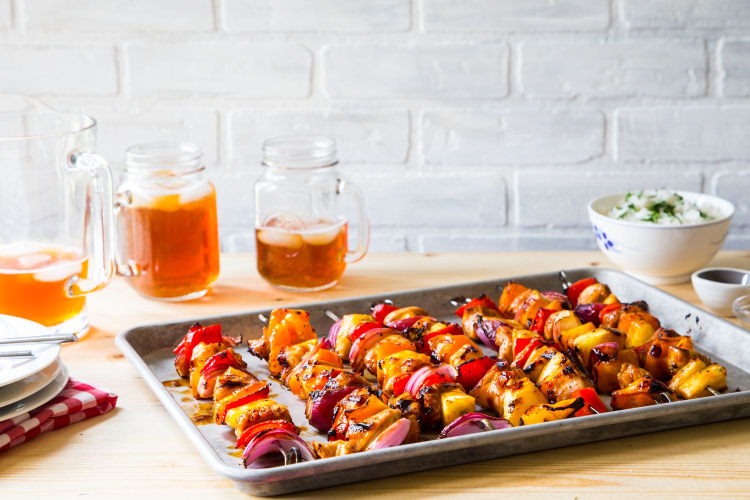 Tropical BBQ chicken skewers with veggies on a tray.