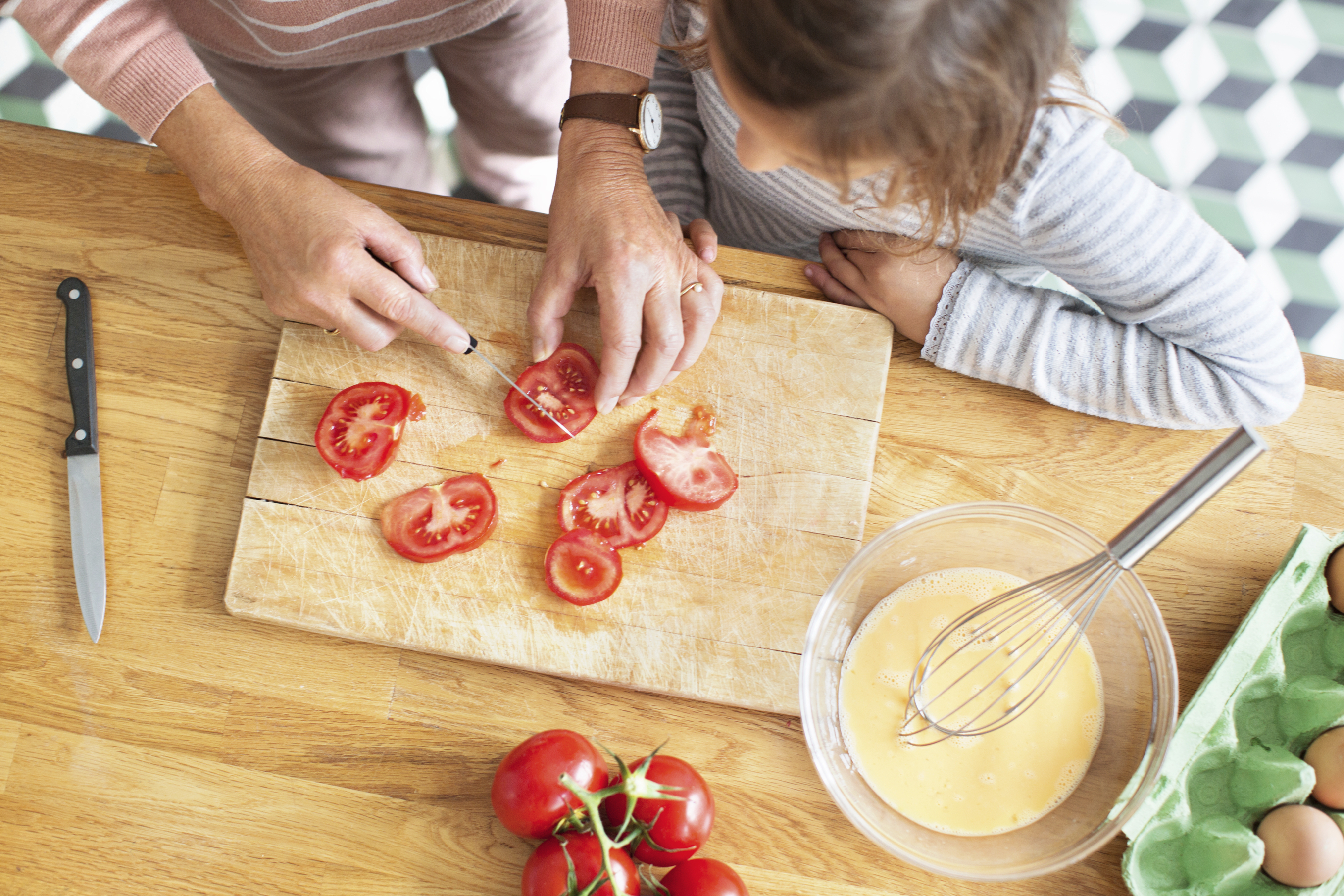 Woman cutting tomatoes while a young child watches.