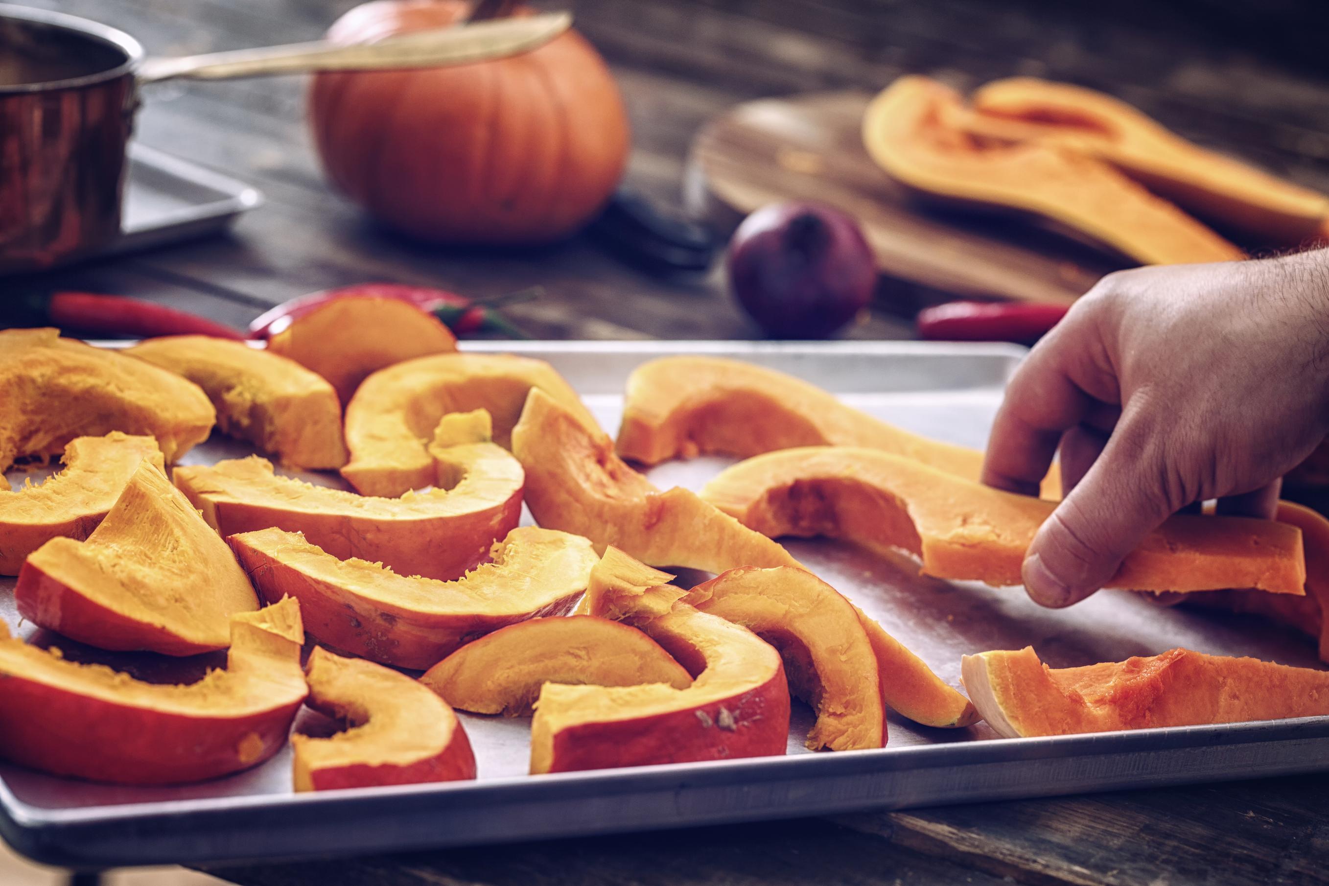 Sliced pumpkin on a baking sheet for roasting.