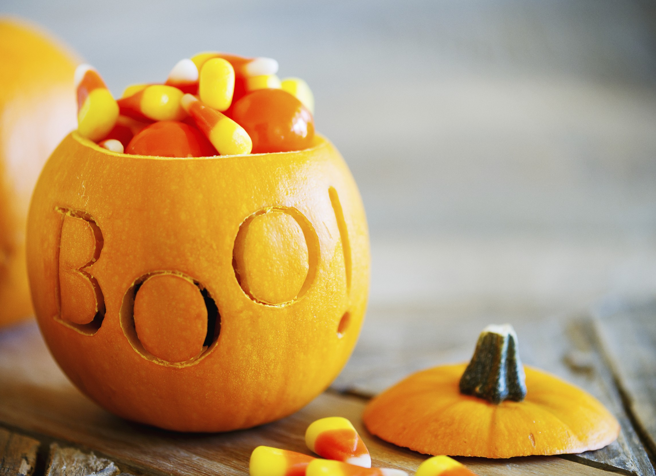 Colorful carved halloween pumpkin filled up with traditional candy corn