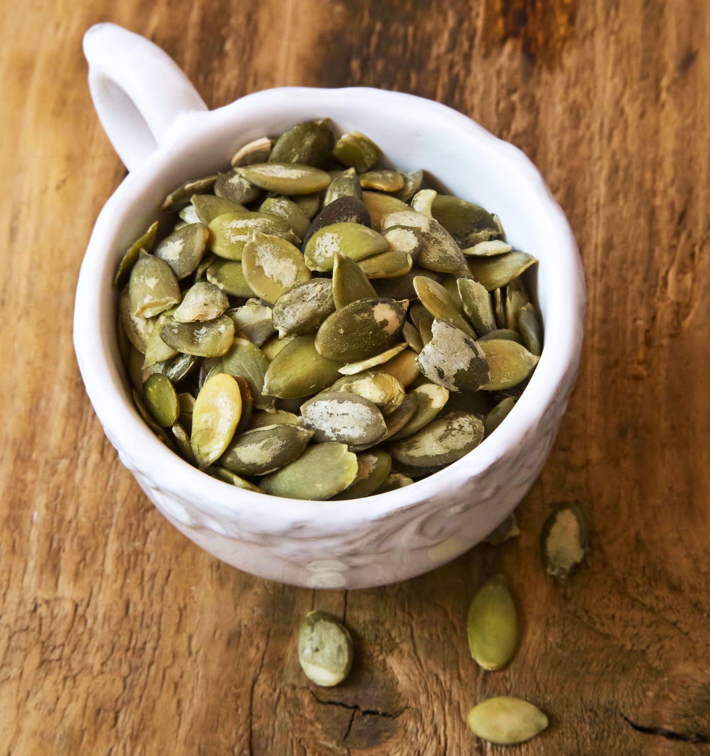Roasted pumpkin seeds in a white cup.