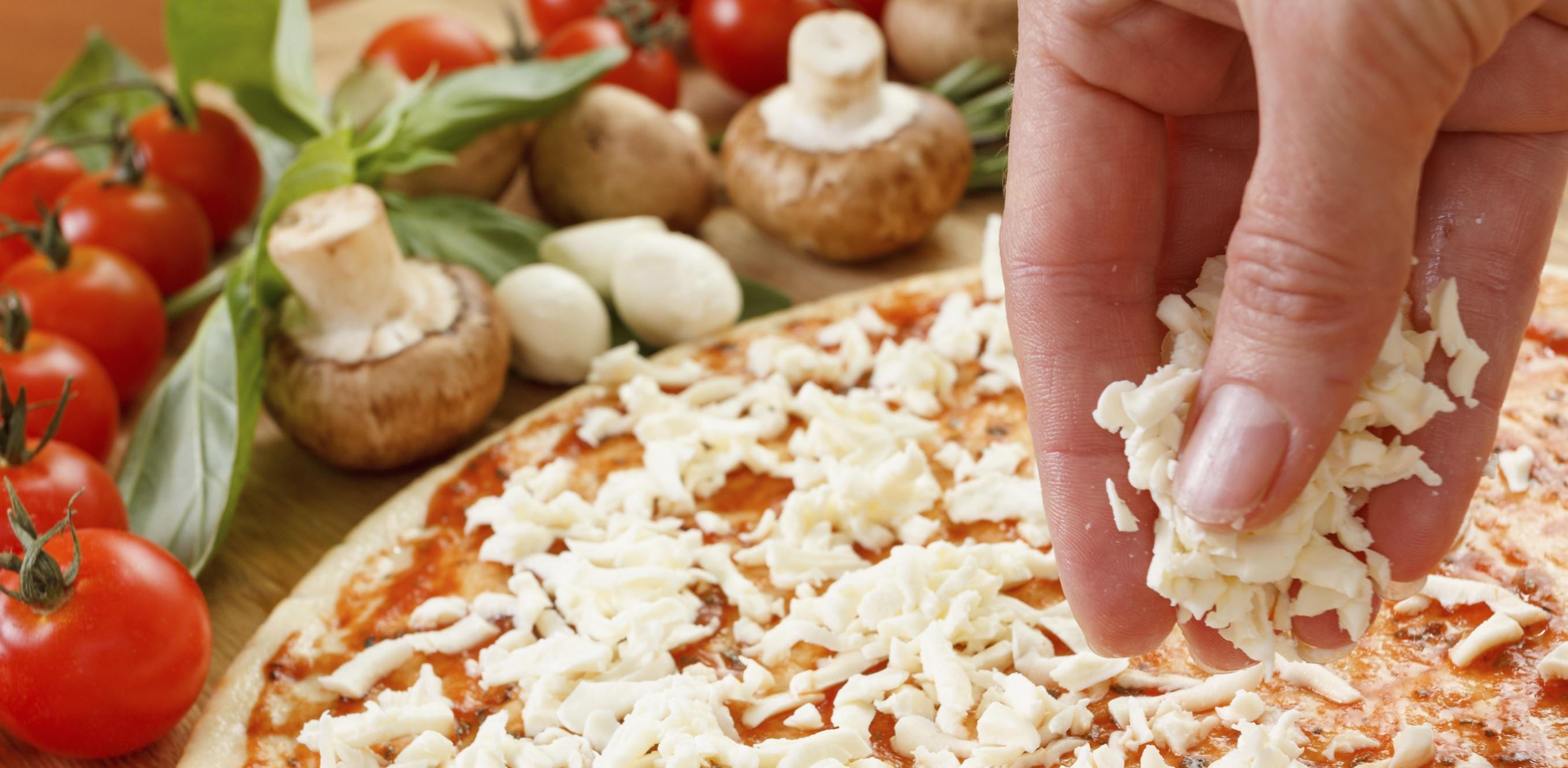 Spreading mozzarella on a pizza with pizza toppings in the background.
