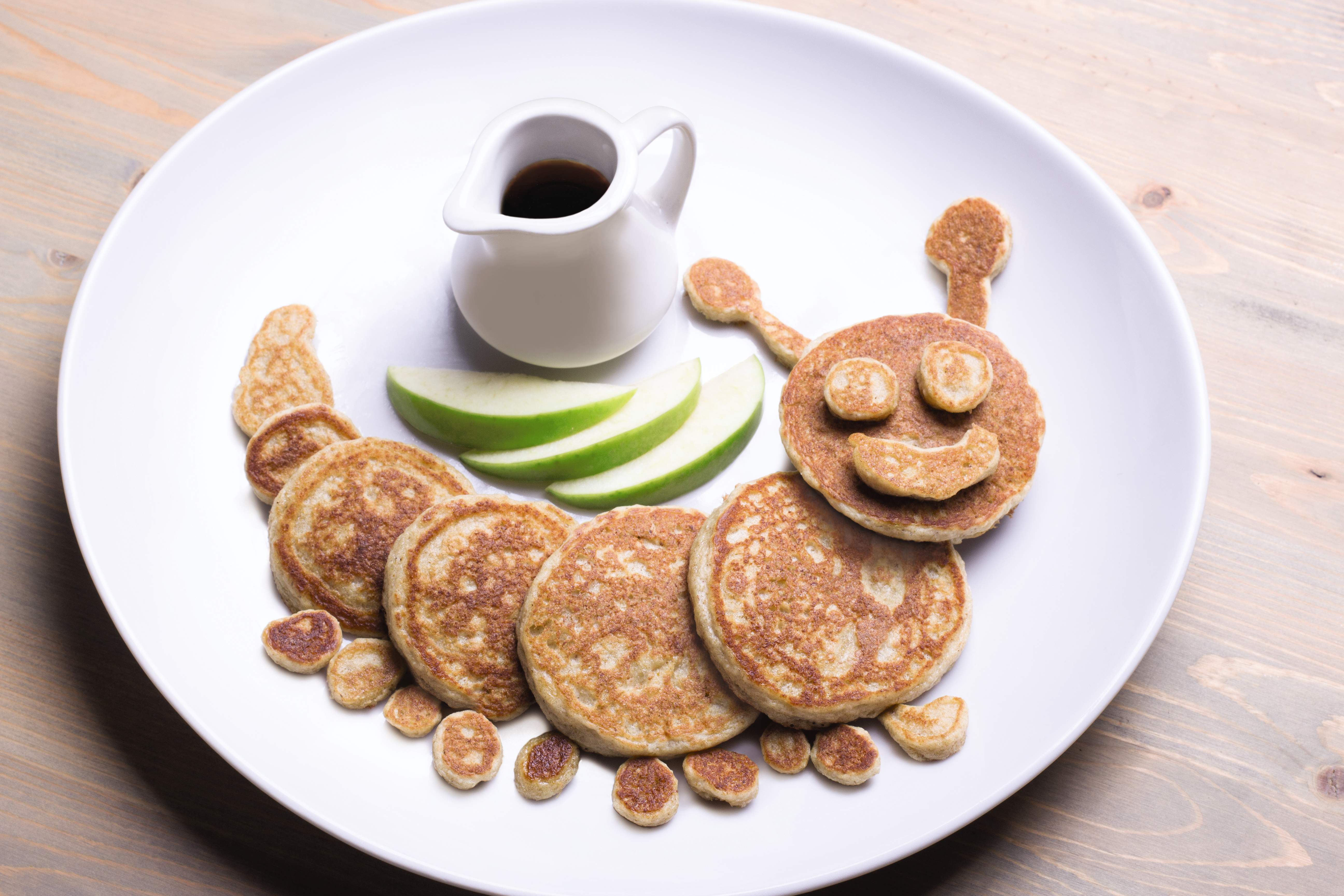 Oatmeal and apple pancakes with syrup formed into a caterpillar.
