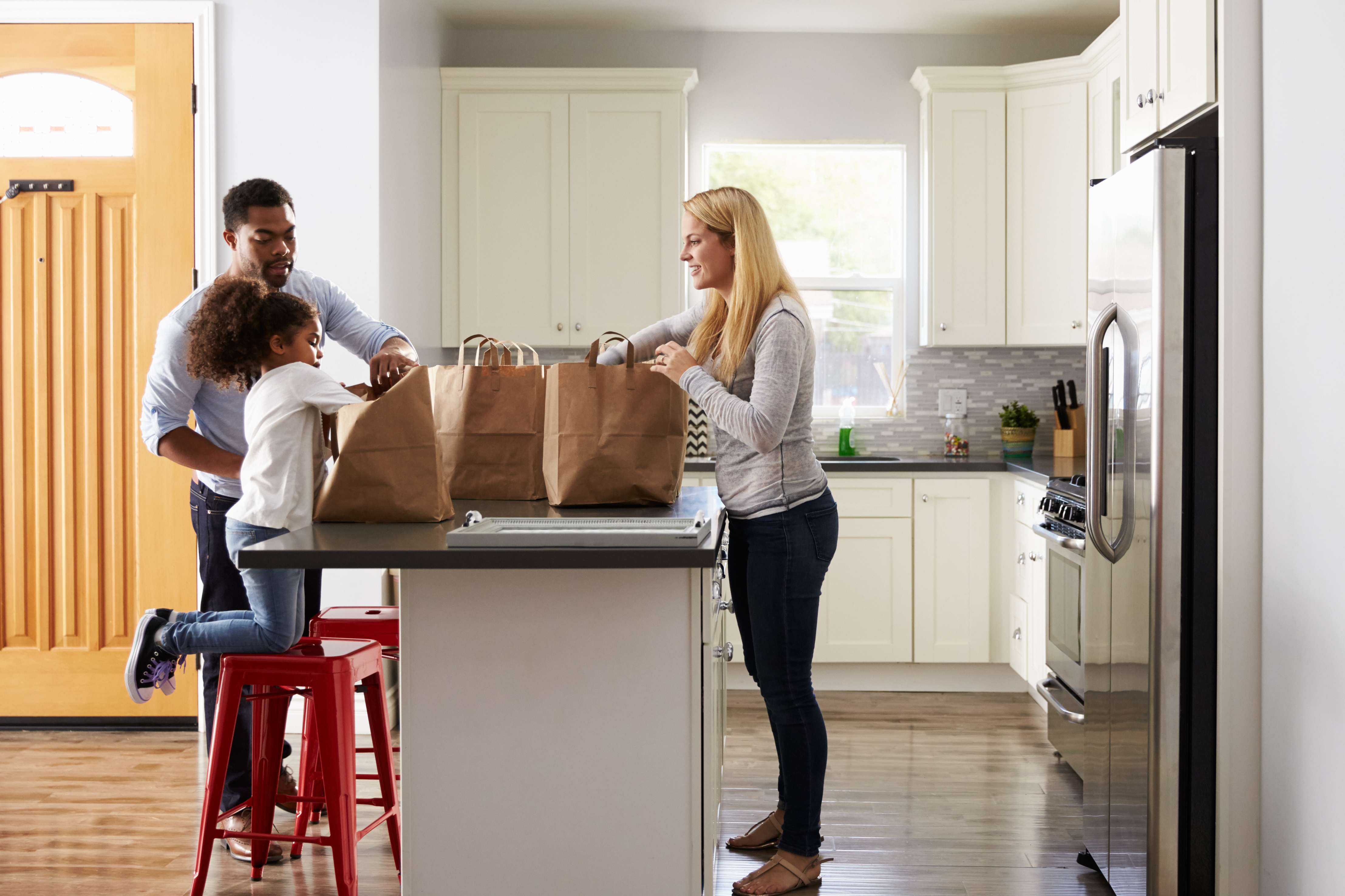 Mixed race couple and their daughter unpacking groceries.