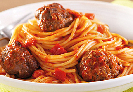 Spaghetti and meatballs in a white bowl.