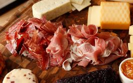 Specially Selected Prosciutto on a wooden serving board with cheese.