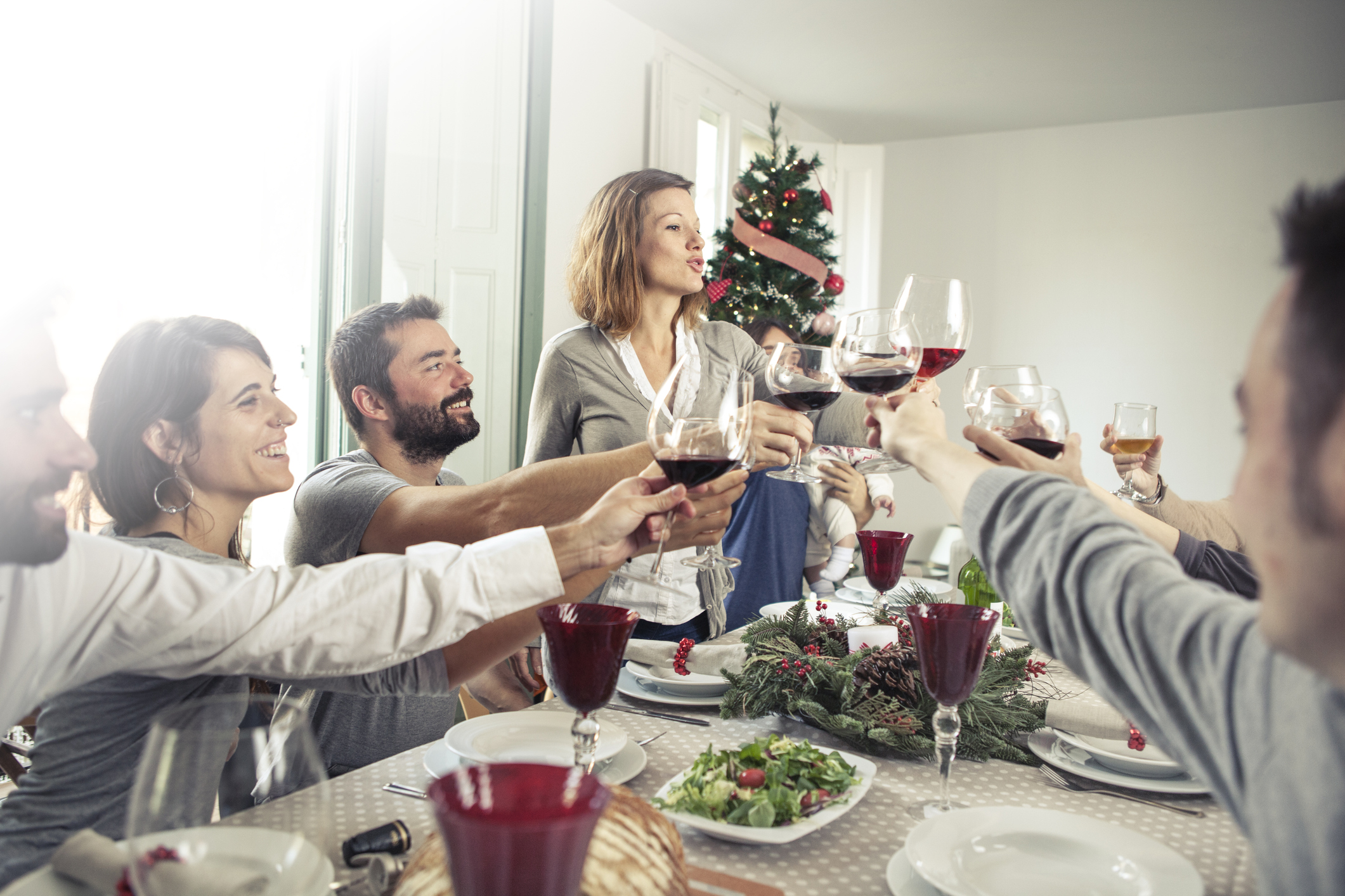 Friends toasting at a Christmas dinner around the table.