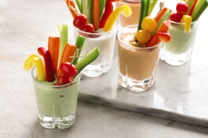 Healthy dip served in a glass with peppers, celery and tomatoes for snacking.