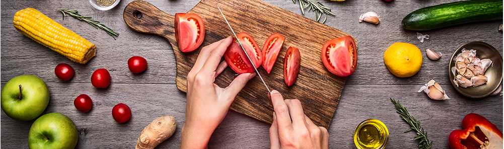 Slicing fresh tomatoes on a wooden cutting board surrounded by other fresh vegetables.