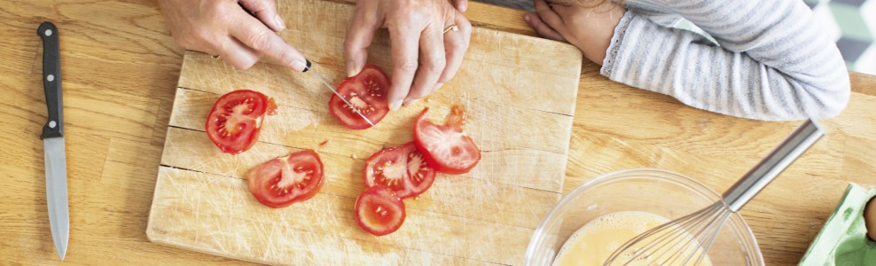 Slicing tomatoes on a cutting board.