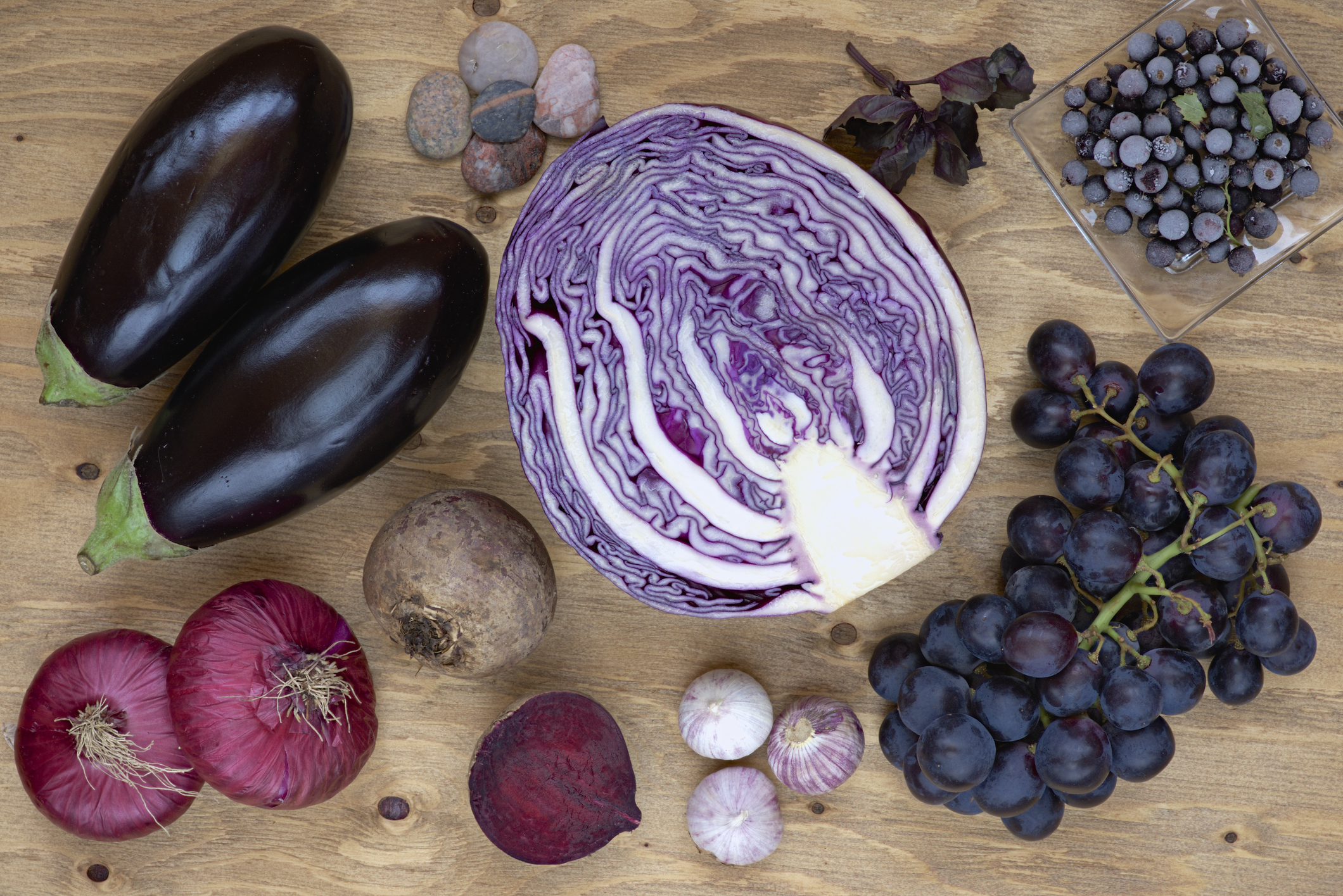 A variety of purple vegetables including eggplant, blueberries and grapes on a wood table.