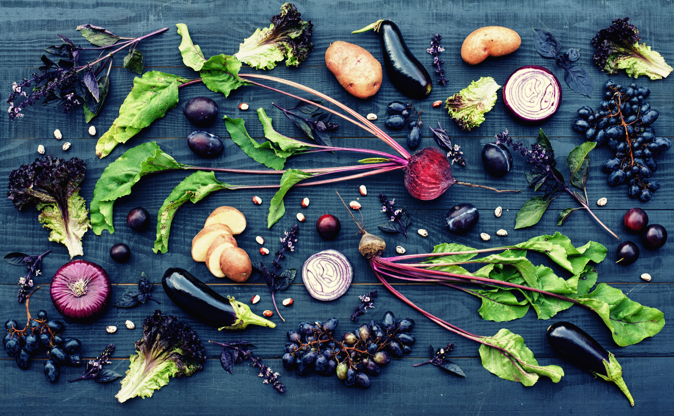 A variety of vegetables spread out on a wooden table including eggplant, radishes and grapes.