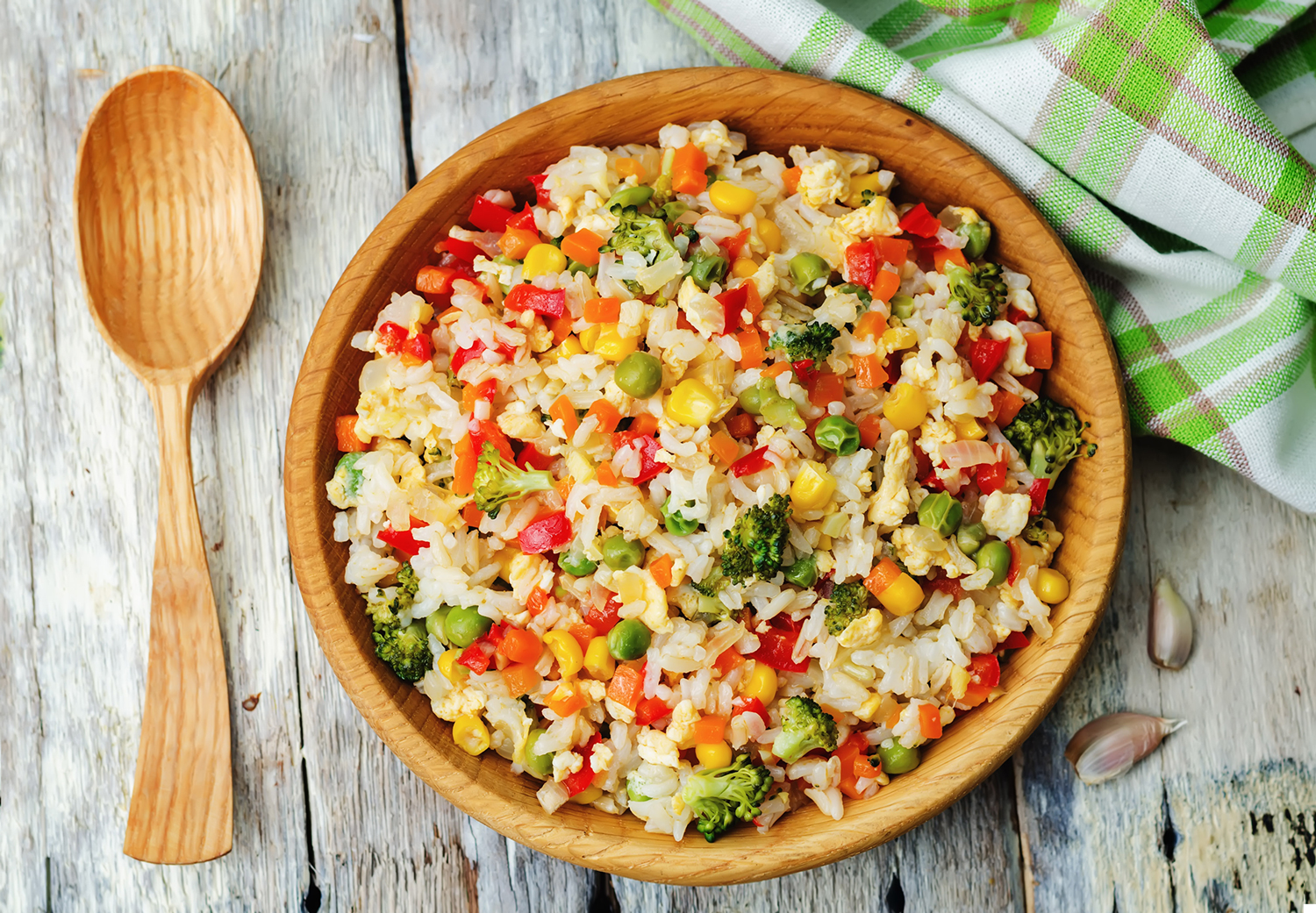 A wooden bowl full of fried rice containing peas, broccoli, corn and peppers.