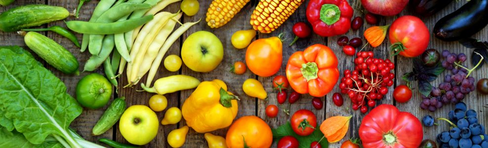 A colorful gradient of vegetables on a wood table.