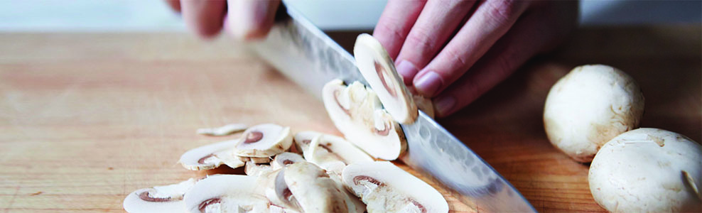 Fresh mushrooms being sliced on a wood cutting board.