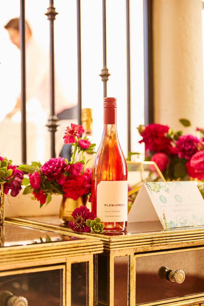 A bottle of Plow & Press Pinot Noir Rosé on a table with flowers.