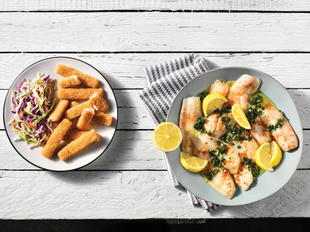 A plate of fish sticks next to a plate of fresh fish garnished with lemon.