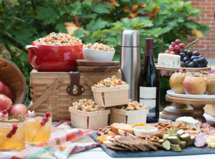 A fall dinner party spread with a charcuterie board, fresh apples and wine.