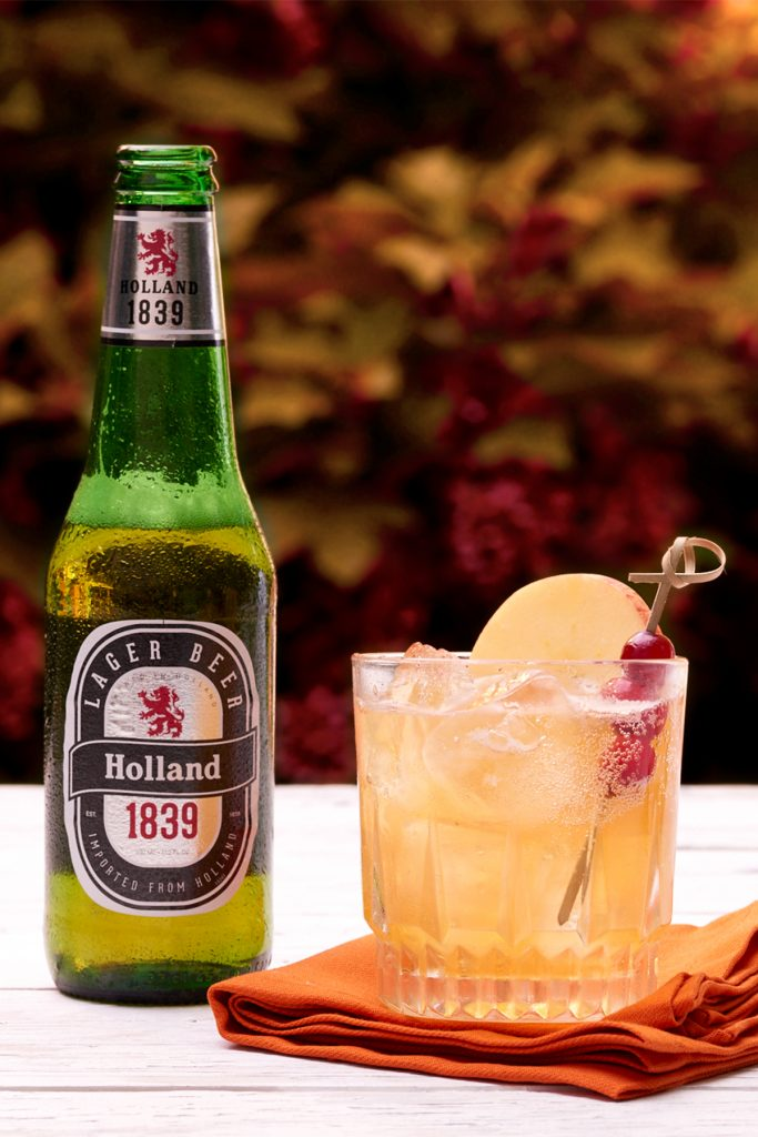 A bottle of Lager Beer with a glass garnished with apple and cranberries.