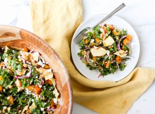 A salad bowl full of Autumn Kale Salad with butternut squash, hazelnuts and apple chips.