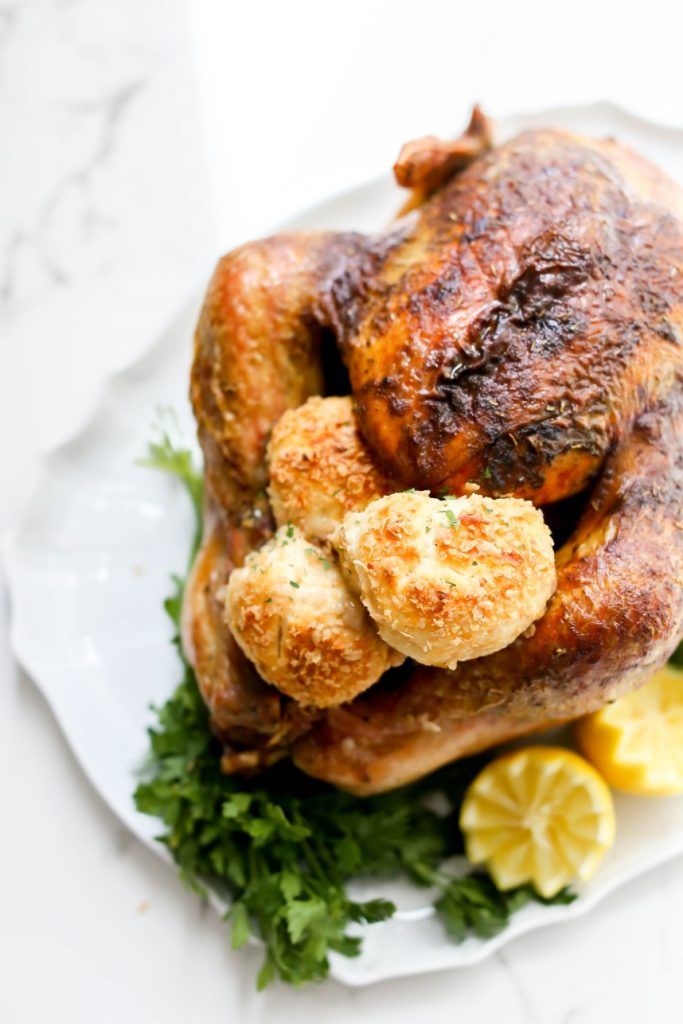 A Herb-Brined Turkey on a serving dish, garnished with lemons.