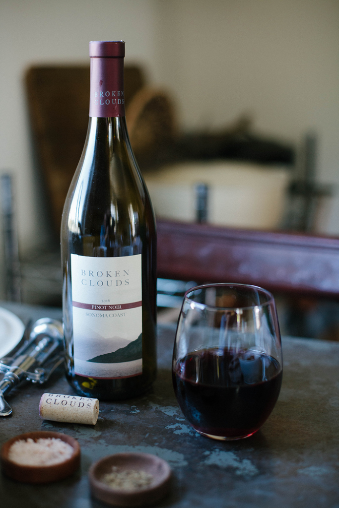 A bottle of Broken Clouds Pinot Noir with a glass full.