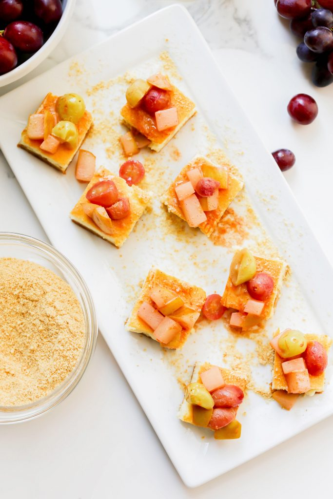 Cheesecake Bites garnished with white wine sautéed pears and grapes on a serving platter.