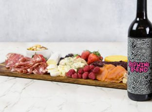 Three bottles of William Wright limited edition reserve wine collection including Chardonnay, Cabernet Sauvignon and a Red Wine Blend in front of a charcuterie board.
