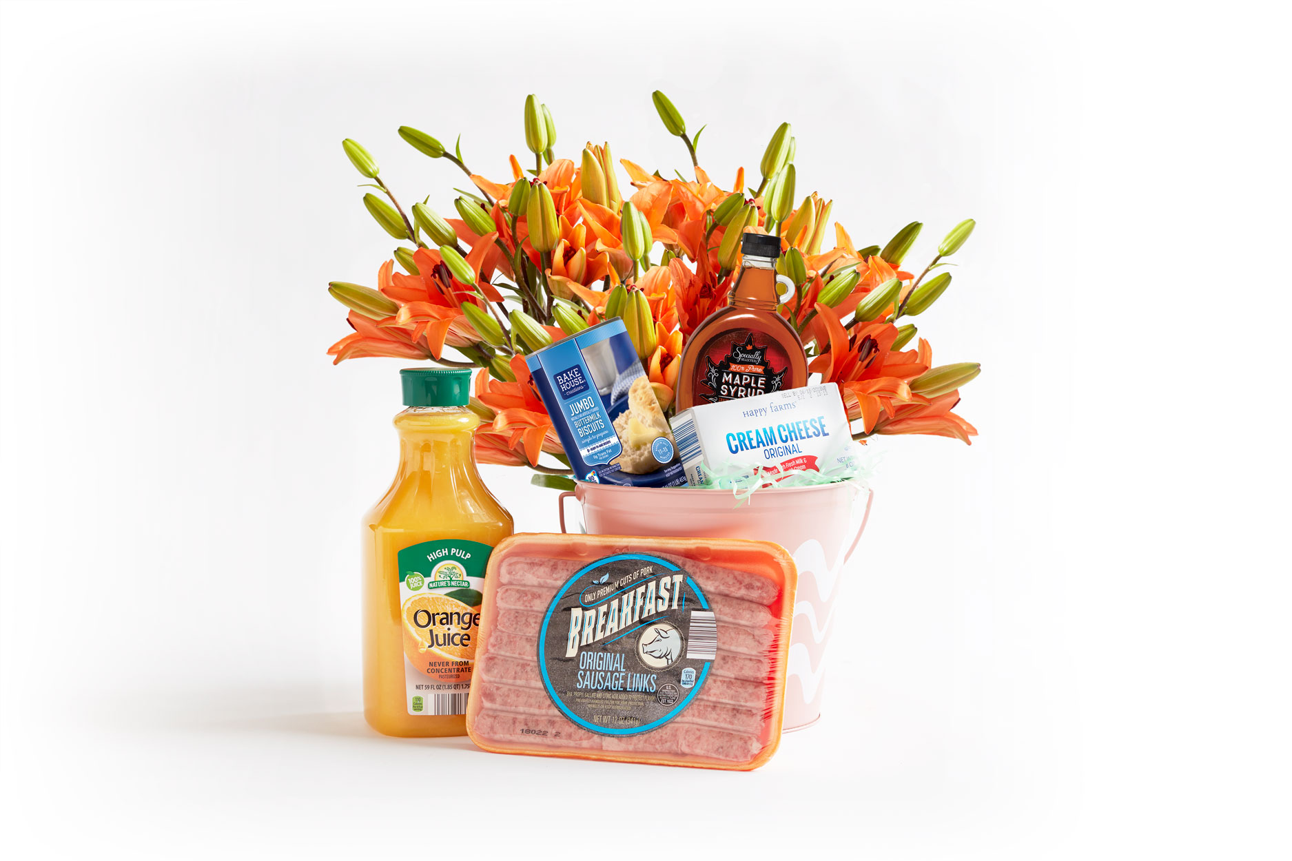 A rise and shine themed Easter basket with breakfast sausage, biscuits, maple syrup and orange juice.
