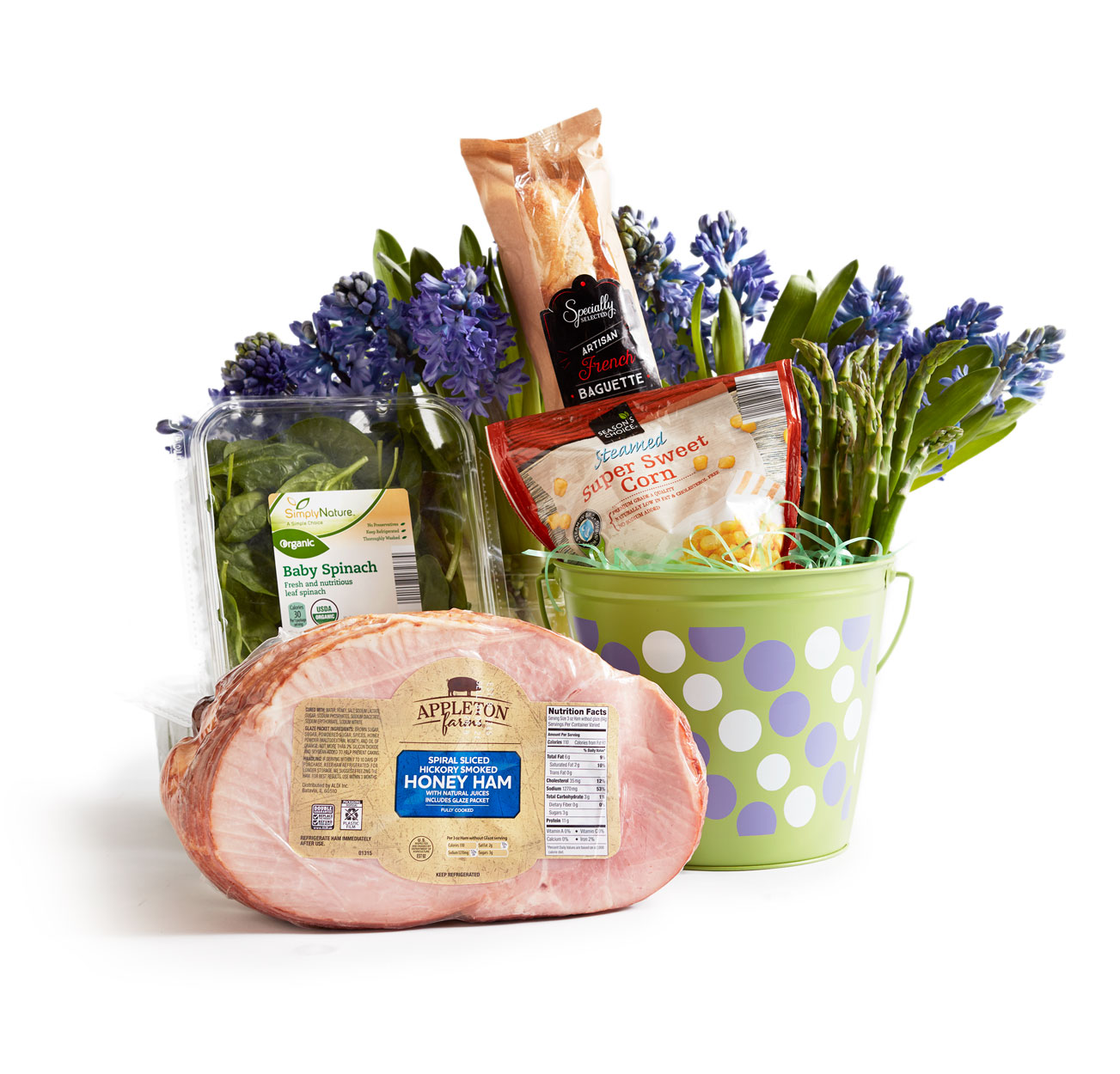 A hostess Easter themed basket with spinach, corn, honey ham and a baguette.