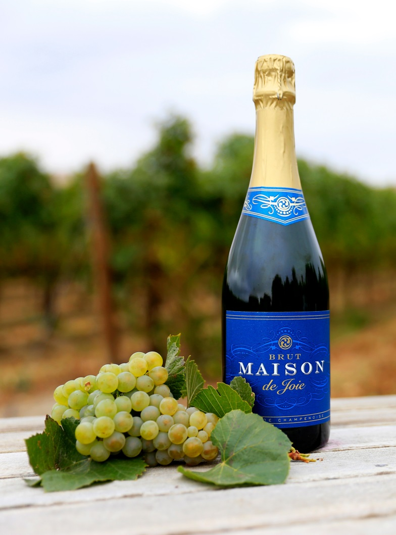 A bottle of Brut Maison de Joie next to a bunch of grapes.
