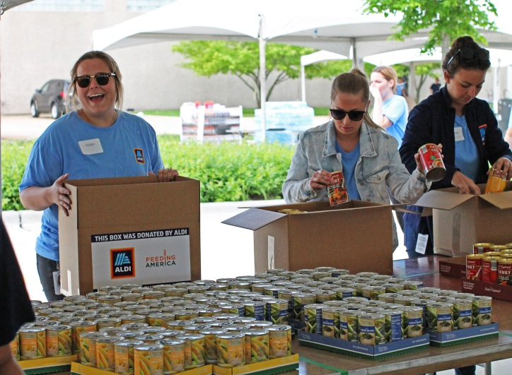 ALDI employees helping fill boxes of canned goods for Feeding America.