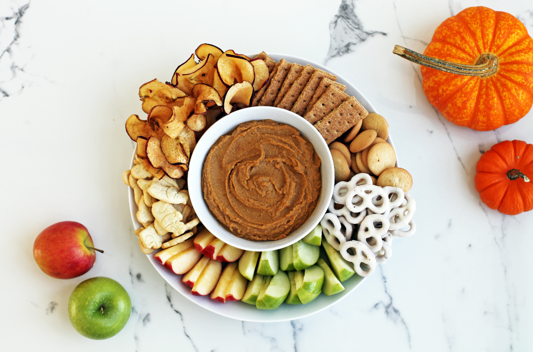 Spicy protein-packed hummus with a variety of snacks for dipping.