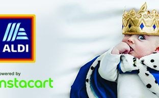 Infant wearing a royal robe and crown, lying on a white fabric background. ALDI logo and Instacart logo